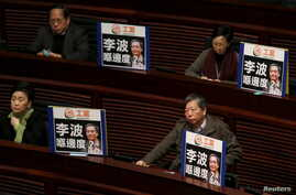 Pro-democracy lawmakers display portraits of Lee Bo, one of the five booksellers who disappeared from a local bookstore, as Chief Executive Leung Chun-ying speaks during his annual policy address at the Legislative Council in Hong Kong, Jan. 13, 2016
