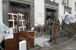 Pro-Russian activists gather at a barricade outside the regional government headquarters in Luhansk, eastern Ukraine, April 30, 2014. Hundreds of pro-Moscow separatists stormed government buildings in one of Ukraine's provincial capitals on Tuesday a