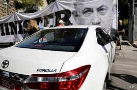 Israeli protesters hold signs as police interrogators arrive to the prime minister's residence in Jerusalem, Aug. 17, 2018. Israeli police are again questioning Prime Minister Benjamin Netanyahu as part of their investigations into corruption allegat