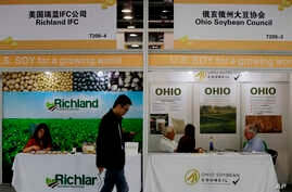 A visitor walks by U.S. soybean companies' booths at the international soybean exhibition in Shanghai, China, April 12, 2018.
