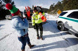 Park ranger Kevin Sturmer, right, tells Sarah Schlesinger of Boulder, Colo., that Trail Ridge Road is blocked to vehicles after a light overnight snow in Rocky Mountain National Park, Dec. 22, 2018, in Estes Park, Colo. The road was unplowed because