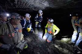 FILE - In this Jan. 13, 2015 file photo, Joe Main, third from left, Assistant Secretary of Labor for Mine Safety and Health, and Patricia Silvey, center, Deputy Assistant Secretary for Operations with MSHA, speak with workers at the Gibson North mine
