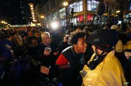 """Lamon Reccord, second from right, yells at a Chicago police officer """"Shoot me 16 times"""" as he and others march through Chicago's Loop Wednesday, Nov. 25, 2015."""