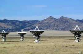 FILE - This Feb. 10, 2017 photo shows a few of the radio antennas that make up the Very Large Array astronomical observatory are positioned on tracks on the Plains of San Augustin west of Socorro, N.M.