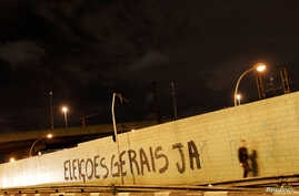 """A man walks past a grafitti on a wall reading """"General Elections, Now"""" in Sao Paulo, Brazil, April 12, 2017."""