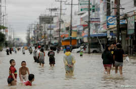 People walk in a flooded street at Muang district in Nakhon Si Thammarat Province, southern Thailand, Jan. 6, 2017.