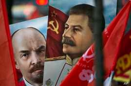 Communist party supporters carry portraits of Soviet founder Vladimir Lenin, left, and Soviet dictator Josef Stalin during a demonstration marking the 100th anniversary of the 1917 Bolshevik revolution in Moscow, Russia, Nov. 7, 2017.