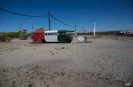 "FILE - A bus painted in a Mexican flag motif and a banner with the Spanish farewell for ""have a nice trip,"" serves as a roadside advertisement for a Chevron station, in Ajo, Arizona, April 4, 2017. In the past month, three large groups of migrants ha"