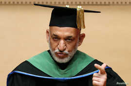 Afghan President Hamid Karzai, wearing an academy gown, delivers a speech as he receives an honorary doctorate at Nippon Sport Science University in Tokyo, July 9, 2012.
