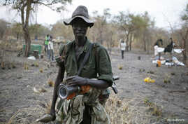 A rebel fighter carries a rocket-propelled grenade (RPG) in a rebel camp in Jonglei State, Feb. 1, 2014.
