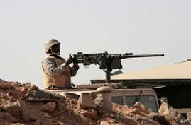 A Saudi soldier sits on top of an armor vehicle as he aims his weapons, on the border with Yemen, at a military point in Najran, Saudi Arabia, April 21, 2015.