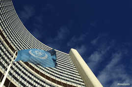 The flag of the International Atomic Energy Agency (IAEA) flies in front of its headquarters during a board of governors meeting in Vienna, Nov. 28, 2013.