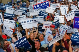 Audience members hold up signs supporting Republican presidential candidate Donald Trump during a campaign rally in Boca Raton, Florida, March 13, 2016.