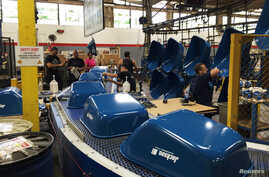 Painted wheelbarrow buckets arrive at the end of the assembly line at the AMES Companies factory, the largest wheelbarrow factory in the world, in Harrisburg, Pennsylvania, June 29, 2017.
