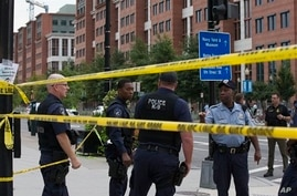 Police work the scene on M Street, SE in Washington near the Washington Navy Yard on Monday, Sept. 16, 2013. The U.S. Navy says one person is injured after a shooting at a Navy building in Washington. Police and emergency crews gathered Monday mornin