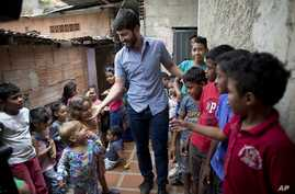 Roberto Patino greets children at a children's center in the La Vega neighborhood of Caracas, Venezuela, Aug. 26, 2018.