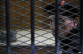 An Egyptian policeman guards the courtroom defendant's cage during a hearing in a court in Cairo, Egypt, April 11, 2015.