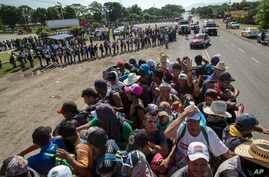 Migrants travel on a truck as others in the back wait in a line for a ride on the road that connects Tapanatepec with Niltepec, Mexico, as a caravan of Central Americans continues its slow march toward the U.S. border, Oct. 29, 2018.