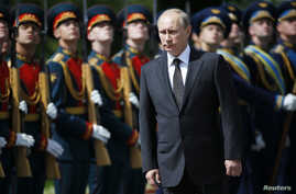 Russia's President Vladimir Putin, front, attends a ceremony to commemorate the anniversary of the beginning of the Great Patriotic War against Nazi Germany in 1941 near memorials by the Kremlin walls in Moscow, June 22, 2014.