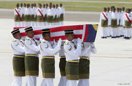The remains of a victim of the downed Malaysia Airlines flight MH17 are carried during a repatriation ceremony at KLIA airport in Sepang, August 22, 2014.