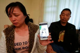 Ronggao Zhang, and her husband Ronggao Zhang, display a photo of them with their missing daughter Yingying Zhang, a University of Illinois student, in Urbana, Illinois,  Nov. 1, 2017.