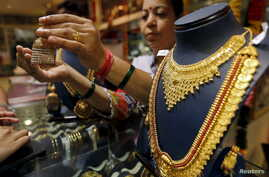 A saleswoman shows a gold earring to customers at a jewellery showroom in Mumbai, India, July 21, 2015.