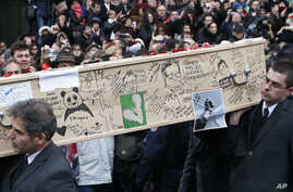Pallbearers carry the casket of Charlie Hebdo cartoonist Bernard Verlhac, known as Tignous, decorated by friends and colleagues of the satirical newspaper Charlie Hebdo, at the city hall of Montreuil, outside east of Paris, Jan. 15, 2015.