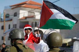 A Palestinian child dressed as Santa Claus holds a Palestinian flag while standing in front of Israeli Border Police during a demonstration against Israel's separation barrier in the West Bank village of Al-Masara, near Bethlehem, Dec. 20, 2013