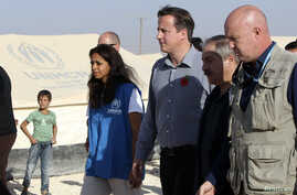 Britain's Prime Minister David Cameron (3rd R) walks with Jordanian Foreign Minister Nasser Judeh (2nd R) and United Nations High Commissioner for Refugees (UNHCR) representative to Jordan Andrew Harper (R) during his visit to Al-Zaatri refugee camp