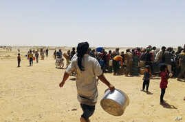 Syrian refugees gather for water at Ruqban border camp in northeast Jordan. Syrian refugees and international aid officials say little water and no food has reached 64,000 Syrian refugees stranded in the desert since Jordan sealed its border in respo
