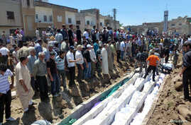 People gather at a mass burial for the victims purportedly killed during an artillery barrage from Syrian forces in Houla in this handout image provided by Shaam News Network, May 26, 2012.