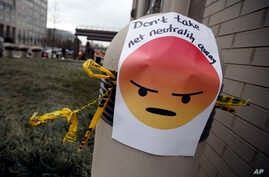 "FILE - A sign with an emoji that reads ""Don't take net neutrality away"" is posted outside the Federal Communications Commission (FCC), in Washington, Dec. 14, 2017."