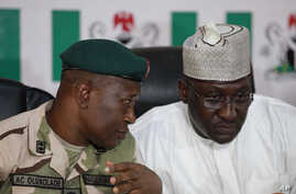 Brig. Gen. Chris Olukolade, Nigeria's top military spokesman, left, talks with Director General, National Orientation Agency, Mike Omeri, during a press conference on the abducted school girls in Abuja, Nigeria, May 12, 2014.