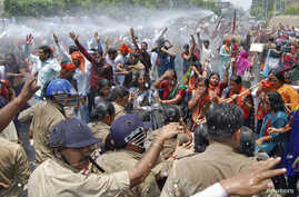Supporters of Bharatiya Janata Party (BJP) are sprayed with a water cannon as police try to stop them from moving toward the office of Akhilesh Yadav, the chief minister of the northern Indian state of Uttar Pradesh, during a protest against the rec