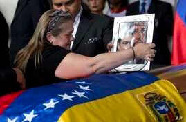 Luz Alban, the sister of opposition activist Fernando Alban, places a framed portrait of her brother shadowed by an image of Jesus Christ over the flag-draped casket containing his remains, during a ceremony at the National Assembly headquarters, in
