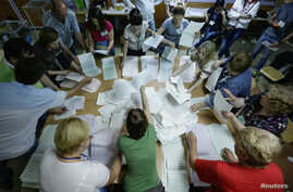 Members of the election commission count ballot papers in a polling station in Kyiv, May 25, 2014.