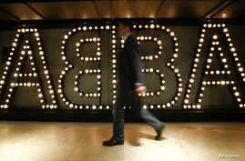 """A man walks past the lit logo of the legendary Swedish pop group ABBA at the new """"ABBA - The Museum"""" in Stockholm, May 6, 2013."""