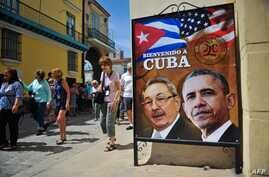 Tourists walk next to a poster of Cuban President Raul Castro and US president Barack Obama in Havana, on March 18, 2016.