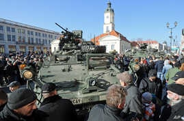 People surround a group of US Army Stryker armored vehicles from the 3rd Squadron of the 2nd Cavalry Regiment, during a stop on the Kosciuszko Market Square to meet residents, in Bialystok, Poland, March 24, 2015.