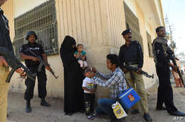 Pakistani policeman stand guard as a health worker administers polio drops to a child during a polio vaccination campaign after a day of an attack by gunmen in Karachi on April 21, 2016.