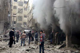 This photo released Dec 13, 2015, by the Douma Revolution News Network on its Facebook page shows Syrians trying to extinguish fire that was caused by Syrian government aerial bombardment on the Damascus suburb of Douma, Syria.