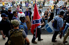 A white supremacists carries the Confederate flag as he walks past counter demonstrators in Charlottesville, Virginia, Aug. 12, 2017.