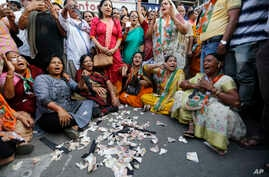 Supporters of India's main opposition Congress party tear toy currency notes and shout sloganS during a protest on the first anniversary of the Nov. 8 demonetization announcement, in Ahmadabad, India, Wednesday, Nov. 8, 2017.