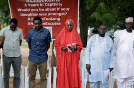 Campaigners observe a minute silent for the remaining Kidnapped schools during their daily sit outs in Abuja, May 9, 2017.