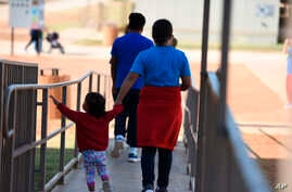 FILE - An Aug. 9, 2018, photo, provided by U.S. Immigration and Customs Enforcement, shows a woman and child walking at a Family Residential Center in Dilley, Texas. A mother and daughter deported to El Salvador were returned to a facility in Dilley
