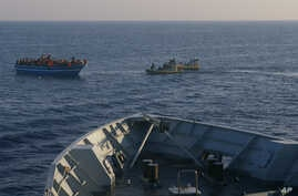 In this photo released by the Italian Navy Wednesday, April 9, 2014, Italian Navy's dingies approach a boat carrying migrants along the Mediterranean sea, off the Sicilian island of Lampedusa