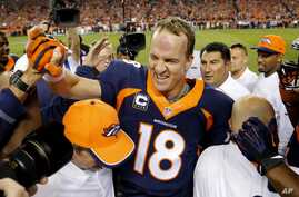 Peyton Manning celebrates his 509th career touchdown pass with teammates in Denver, Oct. 19, 2014.