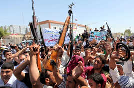 Iraqi men raise up weapons and shout slogans as they demonstration in the central Shiite Muslim shrine city of Najaf on June 14, 2014 to show their support for the call to arms by Shiite cleric Grand Ayatollah Ali al-Sistani.