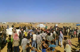 People gather for a food aid distribution at Rukban refugee camp on the Jordan-Syria border, Aug. 4, 2016. The camp is home to some 50,000 Syrians.