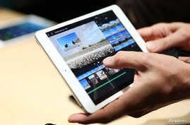 A member of the media holds the new iPad mini with Retnia display during an Apple event in San Francisco, California, Oct. 22, 2013.